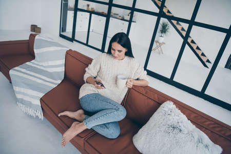 Top high above angle photo of concentrated girl sit on brown leather divan use phone read feednews post comments hold cup with latte wear knitted pullover denim jeans have holidays in house indoors