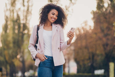 Photo of amazing pretty dark skin wavy lady spend free time walk park after lectures hold telephone reading news enjoy warm autumn fall wear bag jacket jeans outdoors