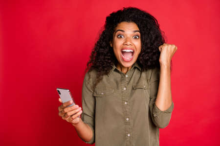 Photo of cheerful rejoicing curly wavy brunette youngster overjoyed with having won competitions shouting screaming brown haired expressing emotions feedback isolated vibrant color background