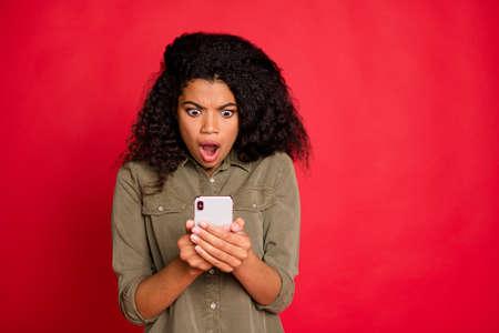 Foto de novia furiosa enojada aterrorizada viendo mala nueva información en su teléfono que expresa emociones negativas en la cara, ondulado, ondulado, elegante, aislado, rojo, vibrante, color, fondo