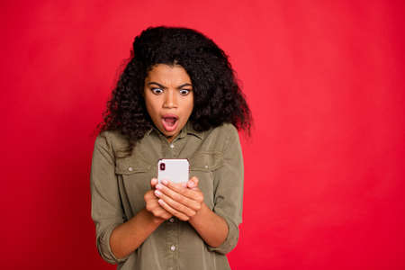 Photo of terrified angry raging girlfriend seeing bad new information on her telephone expressing negative emotions on face curly wavy stylish trendy isolated red vibrant color background