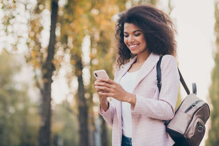 Photo of pretty millennial dark skin wavy lady walk park after lectures hold telephone reading news enjoy warm autumn fall weather wear bag jacket jeans outdoors
