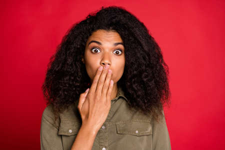 Photo of speechless guilty girl expressing guilty emotions on face covering her mouth with hand wearing green shirt isolated over vivid color background Banco de Imagens