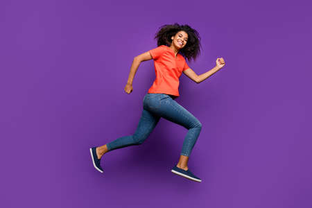 Full length body size photo of side profile curly wavy cheerful nice pretty youngster running forward to shopping mall before holidays isolated over vivid color violet background