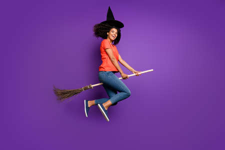 Full length body size side profile photo of cheerful funny witch riding a broomstick expressing emotions wearing orange t-shirt jeans denim cap headwear flying jumping isolated vivid color violet background 版權商用圖片