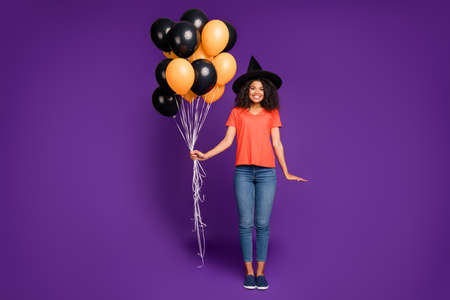 Full length body size photo of cheerful positive cute nice charming pretty girlfriend wearing jeans denim witch hat orange t-shirt holding air balls smiling toothily isolated bright violet color background