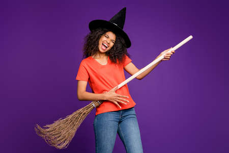 Photo of curly wavy cheerful nice brown haired girlfriend witch playing broomstick guitar imagining screaming her favorite song in jeans denim orange t-shirt isolated vivid purple violet color background Imagens