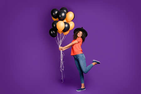 Full length body size side profile photo of cheerful positive cute nice charming pretty girlish youngster holding balloons filled with helium wearing jeans denim smiling toothily playing kind witch isolated vivid violet color background
