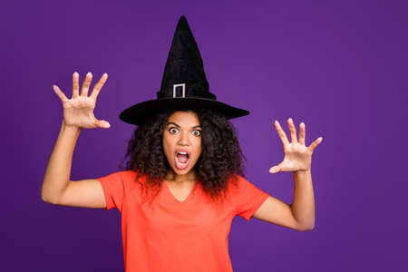 Photo of scary terrible spooky frightful warlock wearing conical cap casting spell to curse you with horrifying facial expression in orange t-shirt isolated over vivid color violet background