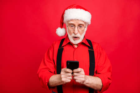 Close-up portrait of his he nice amazed wondered stunned bearded Santa Claus using digital device browsing internet online isolated over bright vivid shine vibrant red background