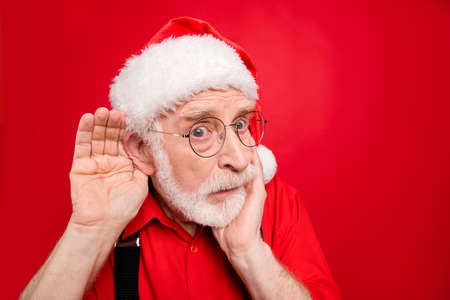 Close-up portrait of his he nice stunned amazed curious suspicious bearded Santa Claus trying to overhear what you say isolated over bright vivid shine vibrant red background