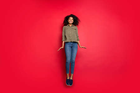 Full length body size photo of cheerful positive cute youngster wearing jeans denim shirt footwear jumping up isolated over vivid color background