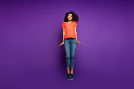 Full length body size photo of cheerful positive pretty sweet beautiful girl wearing jeans denim stretching up jumping isolated violet bright color background