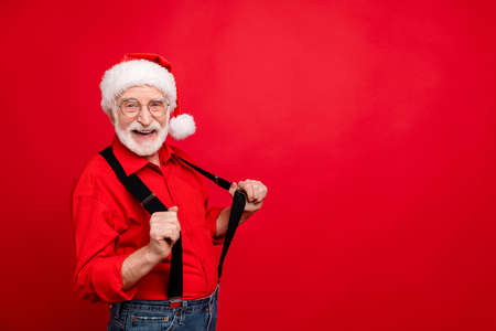 Portrait of his he nice trendy funny cheerful cheery glad bearded Santa Claus pulling suspenders having fun copy space isolated over bright vivid shine vibrant red background