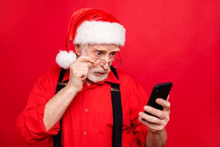 Portrait en gros plan de son père Noël barbu stupéfait, il se demandait à l'aide d'un appareil numérique lisant des informations en ligne sur Internet isolé sur un fond rouge vif et brillant