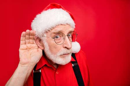 Nahaufnahme seines netten, ernsten, verdächtigen, bärtigen Weihnachtsmannes, der versucht zu hören, was Sie sagen, sprechen Sie ihn einzeln über hell leuchtendem, leuchtend rotem Hintergrund Standard-Bild