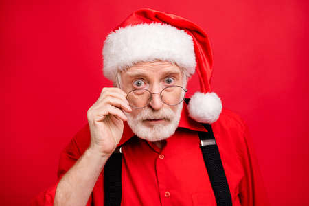 Close-up portrait of his he nice stunned amazed serious wondered bearded Santa Claus omg putting specs off isolated over bright vivid shine vibrant red background Reklamní fotografie
