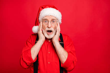 Close-up portrait of his he nice amazed stunned cheerful cheery glad bearded Santa showing omg expression isolated over bright vivid shine vibrant red background Reklamní fotografie
