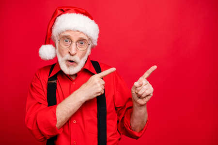 Close-up portrait of his he nice amazed stunned wondered bearded Santa pointing two forefingers aside ad copy space isolated over bright vivid shine vibrant red background