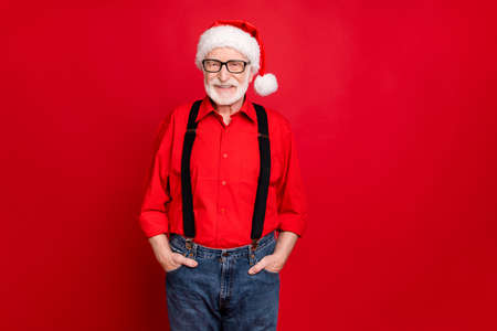Portrait of his he nice trendy cheerful kind content bearded Santa Claus wearing eyewear holding hands in pockets isolated over bright vivid shine vibrant red background