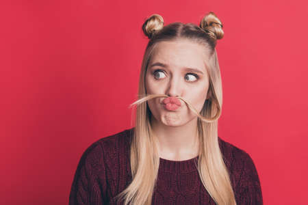 Photo of pretty lady making false moustache with curl funny expression looking wondered to empty space wear knitted pullover isolated pastel red color background Banco de Imagens