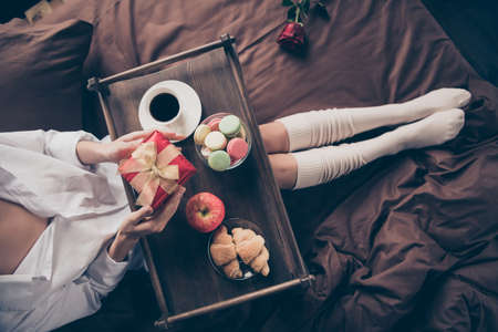 Cropped top above high angle view of nice girl sitting on bed long legs wearing gaiters holding in hands romance gift eating fresh delicious homemade baked snack sweets on sheets linen at house