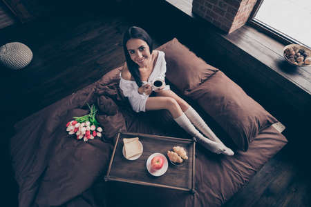 Top above high angle view of nice attractive lovely sweet charming cheerful dreamy girl sitting on bed enjoying romantic surprise drinking coffee industrial brick wood loft modern interior style room