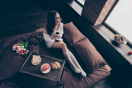 Top above high angle view of nice attractive cheerful cheery dreamy girl sitting on bed enjoying surprise idyllic harmony life drinking coffee industrial brick wood loft modern interior style house