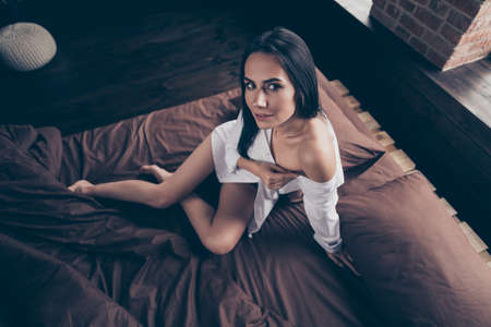 Above high angle view of her she nice-looking attractive lovely lovable pretty girl sitting on bed foot teasing undressing at industrial brick wood loft modern interior style flat house