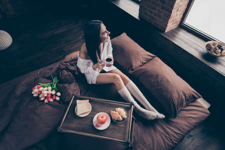 Top above high angle view of nice attractive lovely charming cheerful cheery dreamy girl sitting on bed enjoying romantic breakfast 8 March at industrial brick wood loft modern interior style room Stock fotó