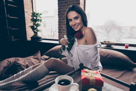 Portrait of her she nice attractive charming lovely sweet cheerful cheery girl sitting on bed smelling fresh rose enjoying romance occasion at industrial brick wood loft modern interior style house Banco de Imagens