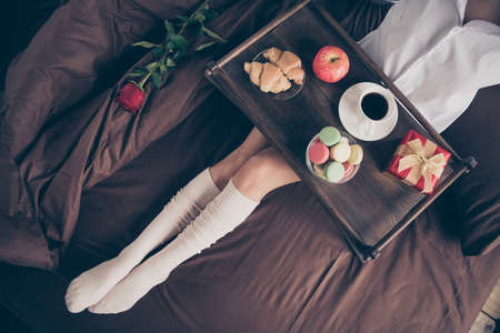 Cropped top above high angle view of nice attractive girl sitting on bed long legs wearing gaiters enjoying romance occasion event fresh snack on sheets linen at house flat indoors Stock fotó