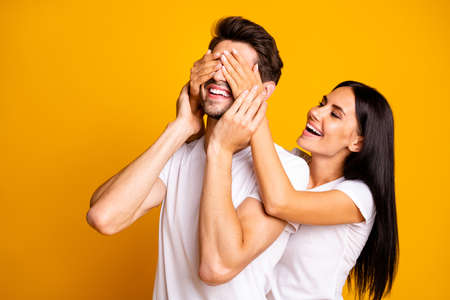 Photo of amazing lady hiding eyes macho guy making unexpected surprise wear casual white t-shirts isolated yellow color background