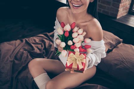 High angle view cropped photo of cute lady sit on bed linen holding in arms little jewelry giftbox and fresh tulips surprise from boyfriend wear white shirt indoors Stock fotó