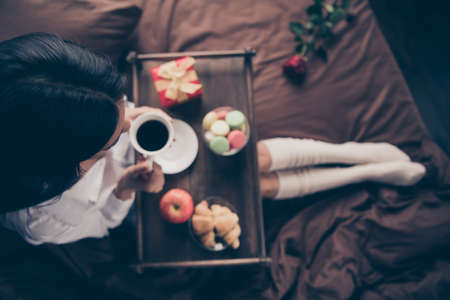 Cropped top above high angle view of nice attractive girl sitting on bed long legs wearing gaiters drinking coffee eating fresh delicious homemade baked snack on sheets linen house flat