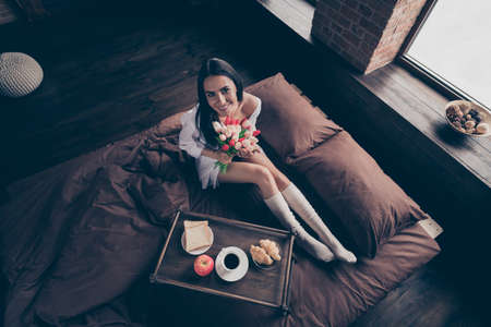 Top above high angle view of her she nice attractive lovely charming pretty cheerful girl sitting on bed enjoying romantic breakfast surprise at industrial brick wood loft modern interior style room Stock fotó