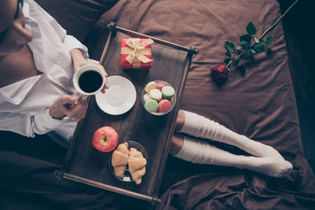 Cropped top above high angle view of nice attractive lovely girl sitting on bed long legs wearing gaiters drinking coffee eating fresh delicious snack on sheets linen house flat apartment