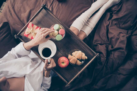 Cropped top above high angle view of nice girl sitting on bed long legs wearing gaiters drinking espresso eating fresh natural delicious homemade sugary baked snack sweets on sheets linen at house