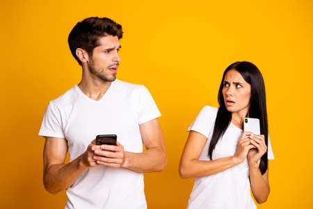 Photo of two people with telephones not trust each other private information wear casual clothes isolated yellow color background