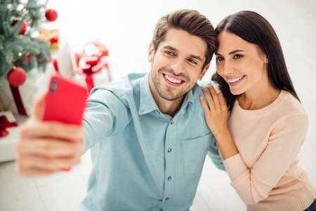 Close up photo of two people cheerful spouses making selfie on cell phone sitting on floor enjoy christmas time x-mas holidays in house indoors