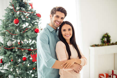 Portrait of two people charming couple with brunet hair hug feel romance enjoy christmas time x-mas holidays in house with newyear decoration wreath indoors