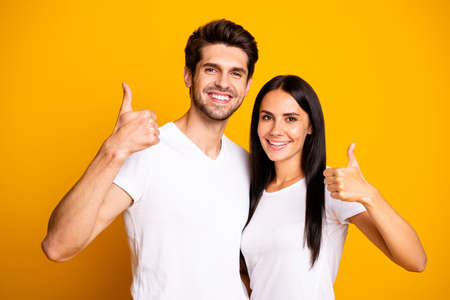 Photo of amazing pair raising thumbs up approving good quality product wear casual outfit isolated yellow color background Stock Photo