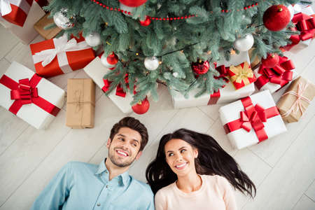 Top high angle photo of two cheerful married people with brunet hair lying on floor celebrate christmas time x-mas holidays in house room indoors