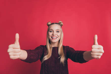 Photo of amazing pretty lady raising thumbs up approving best quality of product wearing knitted pullover isolated pastel red color background