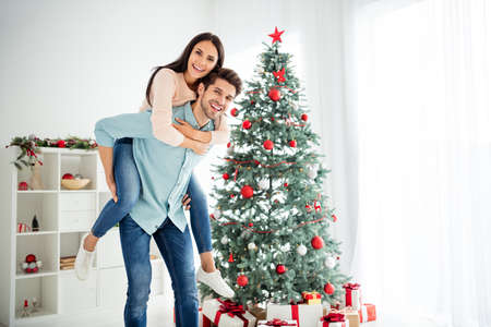 Portrait of two cheerful people romantic couple enjoying christmas, time x-mas holiday in house with evergreen decorative fir tree indoors
