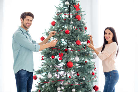 Portrait of two people spouses decorating evergreen fir tree enjoying noel tradition celebrate christmas time prepare for x-mas in house indoors Stock Photo