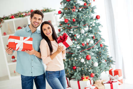 Portrait of two enthusiastic people having brunette hair hold gifts packages enjoy christmas time follow x-mas tradition in house indoors Stock Photo