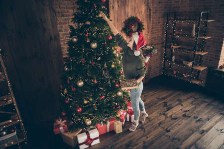 Top above high angle view full size photo of positive girl in santa claus cap knitted pullover hang christmas toys on evergreen fir tree prepare noel party in house full of newyear decoration indoors Stock fotó