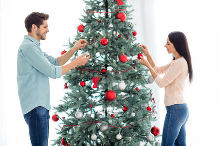 Portrait of two people lovely spouses decorating fir tree holding glass ball prepare for christmas party x-mas holidays s in house indoors