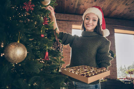 Low angle view photo of positive cheerful brunette hair girl hold box with bauble hang toys prepare for christmas party celebration in house with newyear tinsels garlands indoors